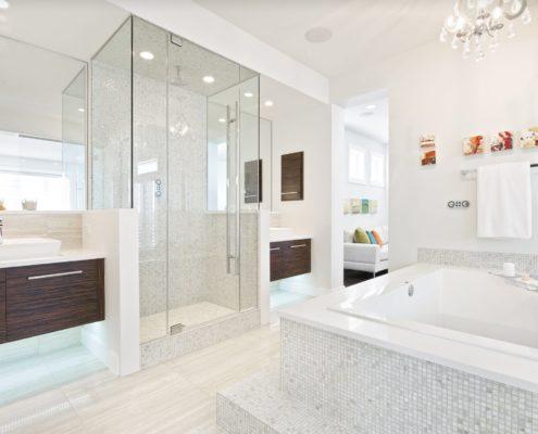 white elongated toilet shower with glass door dark brown color wooden vanities white vessel shape bathtub Marble Master Bathroom small white pedestal sinks frameless shower door